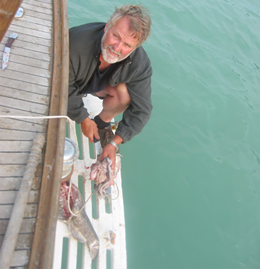 "Captain Rick Cousins cleans a grey cod on the swimming grid (most of this grid gets ripped off in the rocks in the next story ""Ivory Island) of the Audrey Eleanor. The calm before the storm, dinner will soon be served up fresh from the sea."